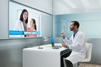 Photo of doctor at desk conferencing remotely with another doctor and patient via computer and screen on the wall.